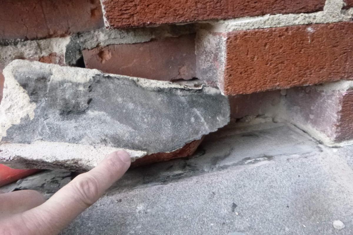 Asphalt-felt separation layer between brick and cast stone